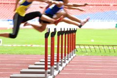 Hurdlers in Action. Image of hurdles in action at a stadium with intentional blurring to portray speed royalty free stock photo
