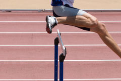 Hurdles. An athlete leaping the hurdles Stock Image