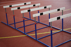 Hurdles on the red running track indoor Stock Images