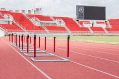 Hurdles on the red running track Stock Photo