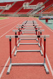 Hurdles on red running track in stadium Stock Images