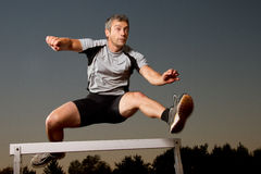 Hurdling in track and field. An athlete running over a hurdle in track and field Royalty Free Stock Photography