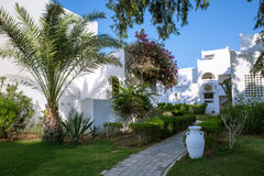 Hurgada, Egypt - 11 August 2014: white wall hotel entrance area with path, palms in the idyllic green garden Stock Image