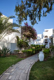 Hurgada, Egypt - 11 August 2014: white wall hotel entrance area with path, palms in the idyllic green garden Royalty Free Stock Photos