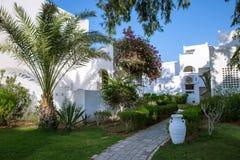 Hurgada, Egypte - 11 Augustus 2014: wit de ingangsgebied van het muurhotel met weg, palmen in de idyllische groene tuin Stock Afbeelding
