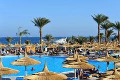 HURGHADA, ЕГИПЕТ - 14-ОЕ ОКТЯБРЯ 2013: Неопознанные люди плавают и загорают в бассейне на роскошном тропическом курорте в Египте Стоковая Фотография