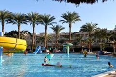 HURGHADA, ЕГИПЕТ - 14-ОЕ ОКТЯБРЯ 2013: Неопознанные люди плавают и загорают в бассейне на роскошном тропическом курорте в Египте Стоковое Изображение