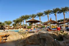 HURGHADA, ЕГИПЕТ - 14-ОЕ ОКТЯБРЯ 2013: Неопознанные люди плавают и загорают в бассейне на роскошном тропическом курорте в Египте Стоковое Фото