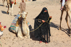 HURGHADA, EGYPT - Apr 24 2015: The old woman-cameleer from Bedouin village in Sahara desert with her camel, Egypt, HURGHADA stock photography