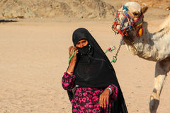 HURGHADA, EGYPT - Apr 24 2015: The old woman-cameleer from Bedouin village in Sahara desert with her camel, Egypt, HURGHADA on Apr Royalty Free Stock Photography
