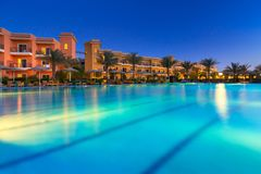 Tropical resort Three Corners Sunny Beach hotel. HURGHADA, EGYPT - APR 9, 2013: Tropical resort Three Corners Sunny Beach in Hurghada at dusk. Three Corners is Stock Photo
