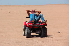 HURGHADA, EGYPT - Apr 24 2015: An young Egyptian man rests lying on his ATV  after desert safari on quad, Egypt, HURGHADA Stock Photos