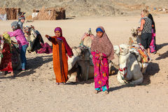 HURGHADA, EGYPT - Apr 24 2015: The young girl-cameleer from Bedouin village in Sahara desert with her camel, shouting inviting Royalty Free Stock Photos