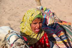 HURGHADA, EGYPT - Apr 24 2015: The young girl-cameleer from Bedouin village in Sahara desert with her camel, shouting inviting Stock Image