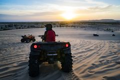 Hurghada, Egypt - December 10, 2018: Young man in safari trip through egyptian desert driving ATV at sunset. Quad bikes safari in. Young man in safari trip stock images