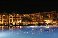 Pool and evening hotel on vacation. People relax in evening near pool royalty free stock photos