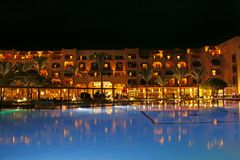 Pool and evening hotel on vacation. People relax in evening near pool stock photos