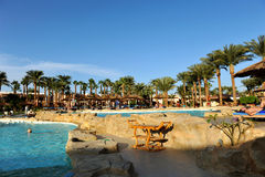 HURGHADA, EGYPT - OCTOBER 14, 2013:Unidentified people swim and sunbathe in the swimming pool at a luxury tropical resort in Egypt Stock Photo