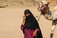HURGHADA, EGYPTE - 24 April 2015: De oude vrouw -vrouw-cameleer van Bedouin dorp in de woestijn van de Sahara met haar kameel, Eg Royalty-vrije Stock Fotografie