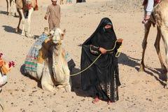 HURGHADA, EGYPTE - 24 April 2015: De oude vrouw -vrouw-cameleer van Bedouin dorp in de woestijn van de Sahara met haar kameel, Eg Stock Fotografie