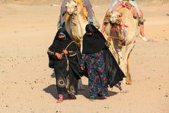 HURGHADA, EGYPTE - 24 April 2015: Oude en jonge vrouw-cameleers van Bedouin dorp in de woestijn van de Sahara met hun kamelen, Eg Stock Fotografie
