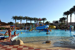 HURGHADA, EGYPTE - OKTOBER 14, 2013: De niet geïdentificeerde mensen zwemmen en zonnebaden in het zwembad bij een luxe tropische  stock afbeelding
