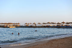 HURGHADA, EGYPTE - OKTOBER 14, 2013: Het zandige strandhoogtepunt van mensen is op de Rode Overzeese kustlijn Het hotel van de lu Royalty-vrije Stock Fotografie