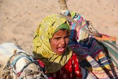 HURGHADA EGYPTEN - April 24 2015: Den unga flickan-cameleer från beduinby i den Sahara öknen med hennes kamel som ropar att invit Fotografering för Bildbyråer