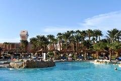 HURGHADA EGYPTEN - OKTOBER 14, 2013: Det oidentifierade folket simmar och solbadar i simbassängen på en lyxig tropisk semesterort royaltyfria bilder