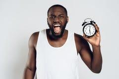 Hurlements fâchés d'homme d'Afro-américain tenant l'alarme photographie stock