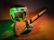 Hurling Equipment Color. A studio shot of a hurling stick, ball, and helmet in colorful green and orange light. irish Stock Photos