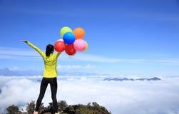 Hurra öppna armar för ung kvinna med ballonger Fotografering för Bildbyråer