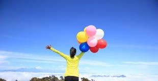 Hurra öppna armar för ung kvinna med ballonger Royaltyfri Fotografi