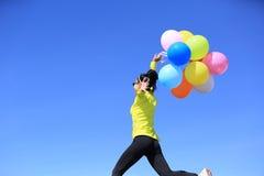 Hurra den unga kvinnan med färgrika ballonger Royaltyfri Bild