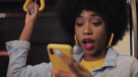 Hurra fira för lycklig afro affärskvinna se smartphonen Ung stads- yrkesmässig lyckad affärskvinna lager videofilmer