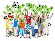 Hurra fotbolllek för folk med flaggan av Brasilien fotografering för bildbyråer