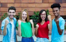 Hurra gruppen av fyra unga vuxna m?nniskor av utveckling y som visar tummar arkivfoton