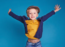 Hurrah!. Little excited boy jumping isolated on blue Royalty Free Stock Image