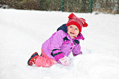 Hurrah, snow. Cute adorable baby crawling in snow in winter park Stock Image