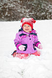 Hurrah, winter. Cute adorable baby sitting on snow in winter park Royalty Free Stock Image