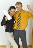 Hurray!. Young, happy business couple. Man is holding keys, woman is holding  some kind of contract. Looking at camera, front view Stock Photo