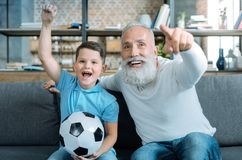 Excited family members watching football at home. Hurray. Extremely happy senior gentleman and his grandson sitting on a sofa and lifting their arms with Royalty Free Stock Photography