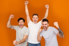 Hurray! Happy Mates Shouting And Celebrating Victory. Over Orange Background royalty free stock photography