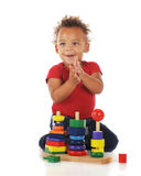 Hurray!  I did it!. An adorable toddler clapping for himself for successfully assembling a colorful stacking toy.  On a white background.  Motion blur on child's Stock Photography