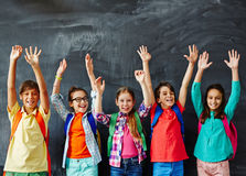 Hurray to school. Schoolkids raising hands at chalkboard Royalty Free Stock Photo