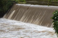 Hurrican Florence - Readdies River Spillway. Brown rain runoff from Hurricane Florence rushes over the spillway on the Readdies River in North Wilkesboro, NC royalty free stock images