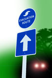 Hurricane evacuation sign. This image is a Hurricane evacuation sign, showing the sign on a highway road, with trees and headlights from a car in the background royalty free illustration