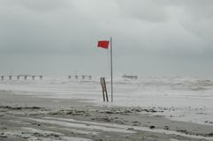 Hurricane Pounding Coast. Damaged pier in background. Red warning flag in foreground Royalty Free Stock Photos