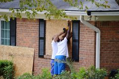 Hurricane Preparation. Two men putting plywood over windows in preparation for a hurricane royalty free stock photos