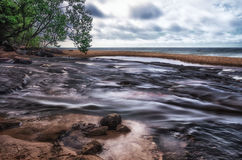 Hurricane river meets Lake Superior in Upper Michigan. Water motion Royalty Free Stock Photo